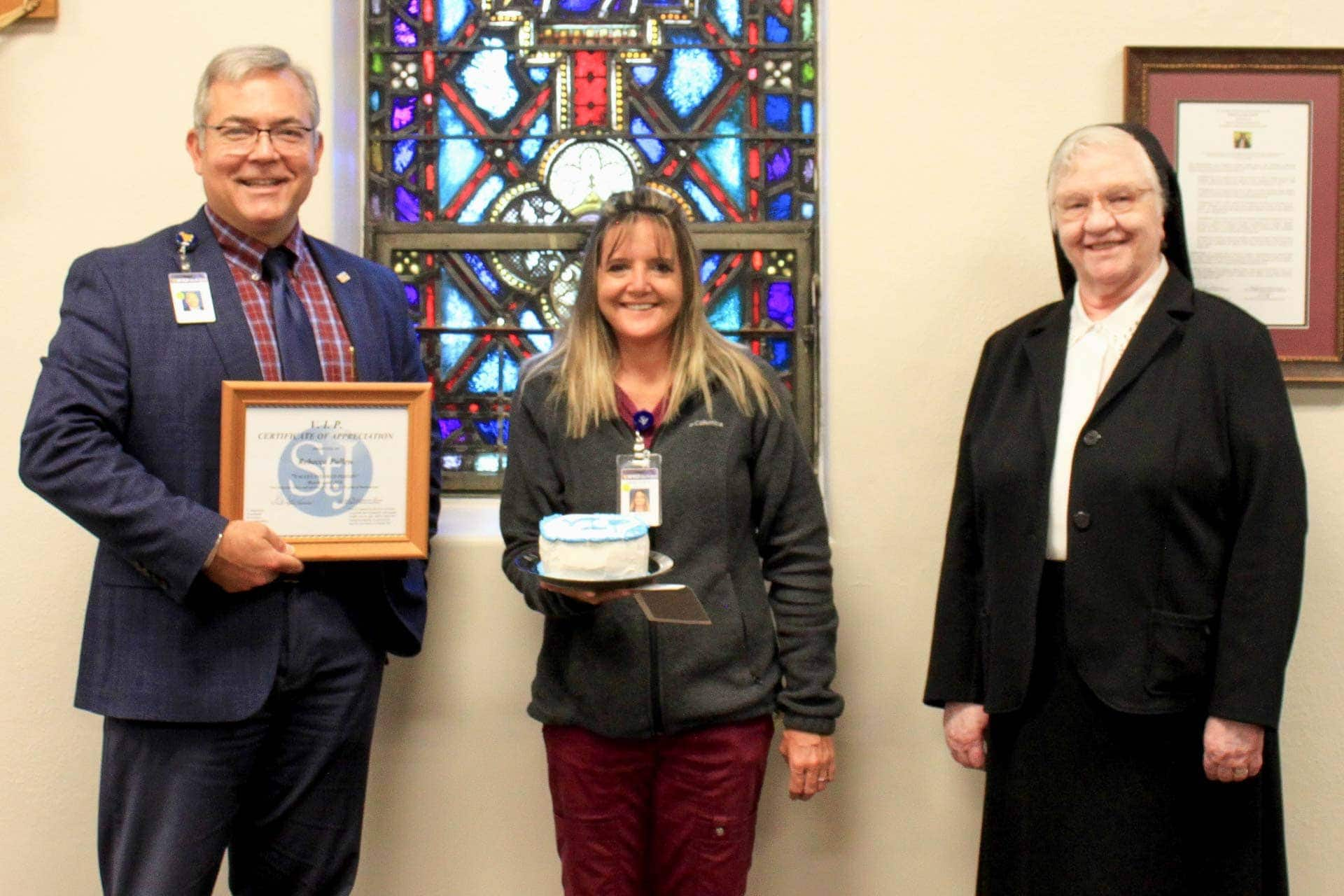 Skip Gjolberg, President of St. Joseph's Hospital, and Sister Francesca Lowis, Vice President of Mission Integration, present the VIP Award to Becky Pullen.