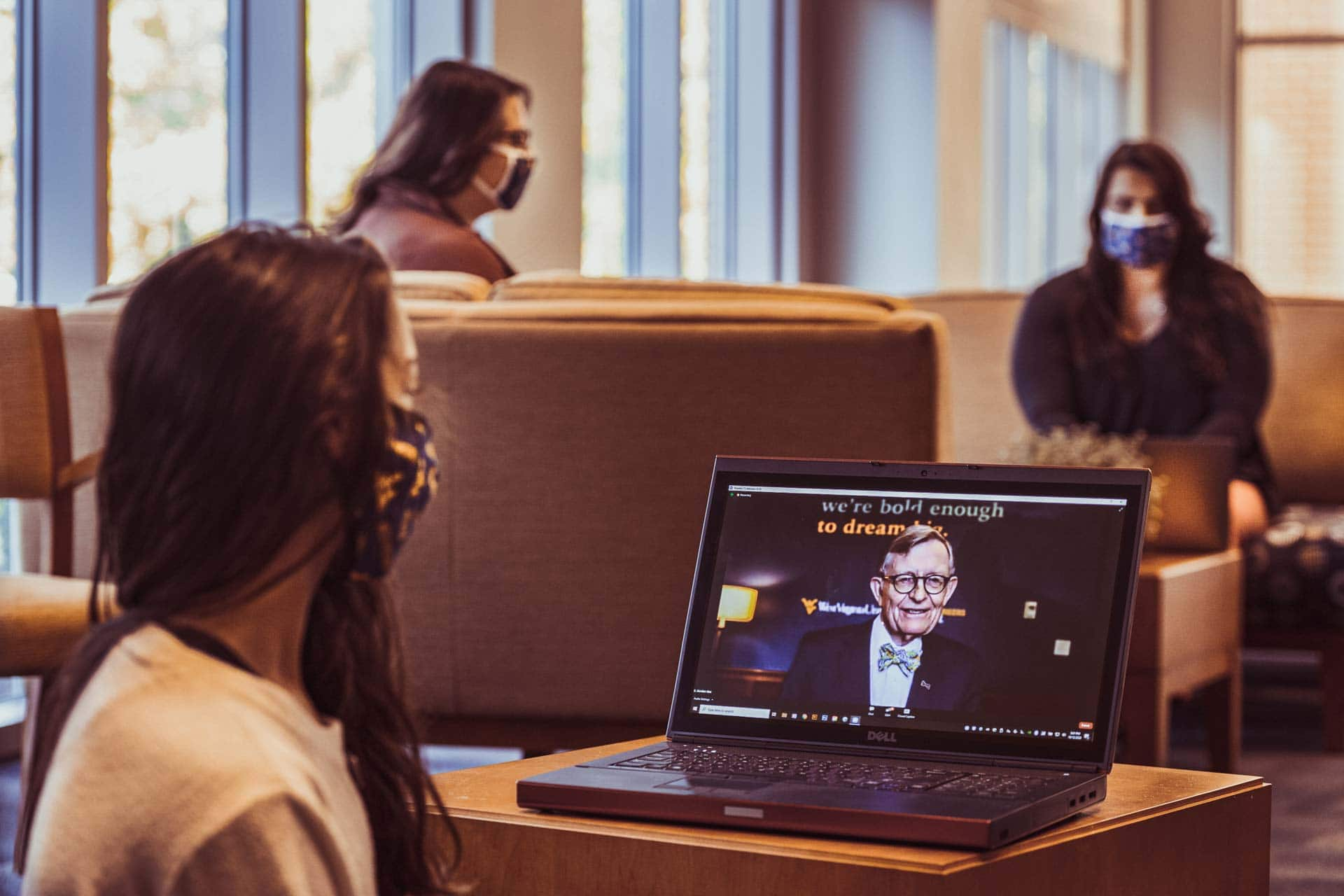 WVU student and visitor center student employ Megan Buchheit and fellow WVU staff Kirsten Swales and Raphy Greco pause their workday to watch the WVU Virtual State of the University during the Covid-19 Pandemic presented by WVU President E Gordon Gee. October 12, 2020. (WVU Photo/Greg Ellis)