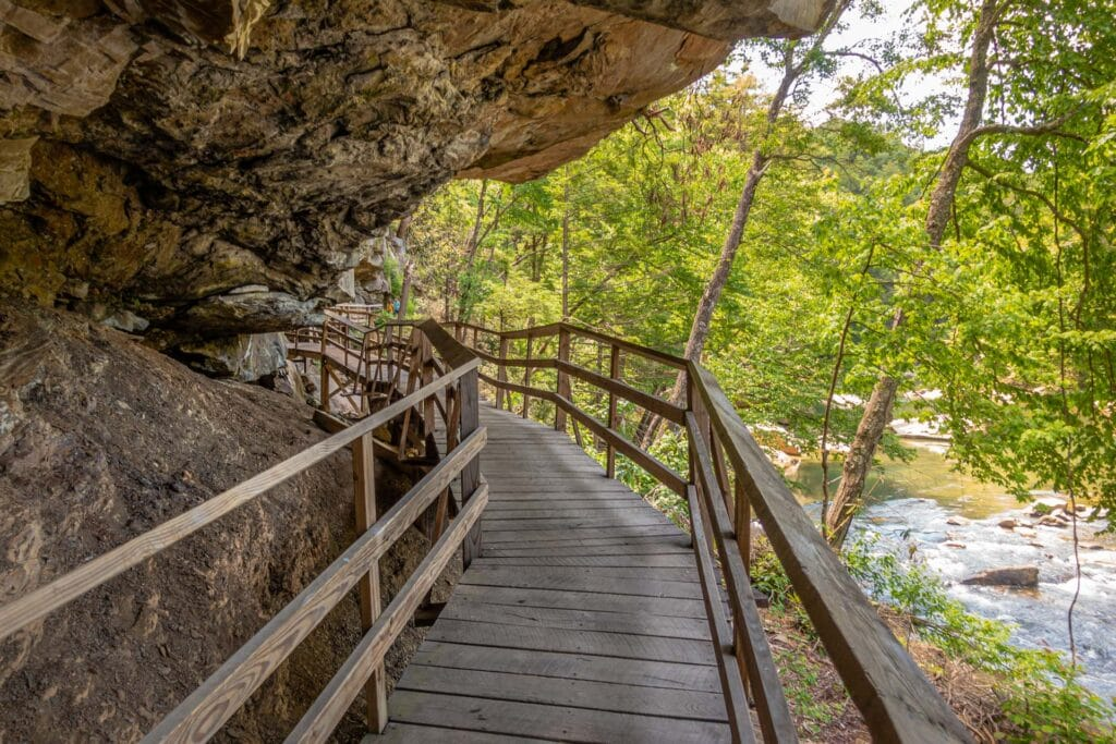 A wooden bridge winds under a rock overhang in Audra State Park.
