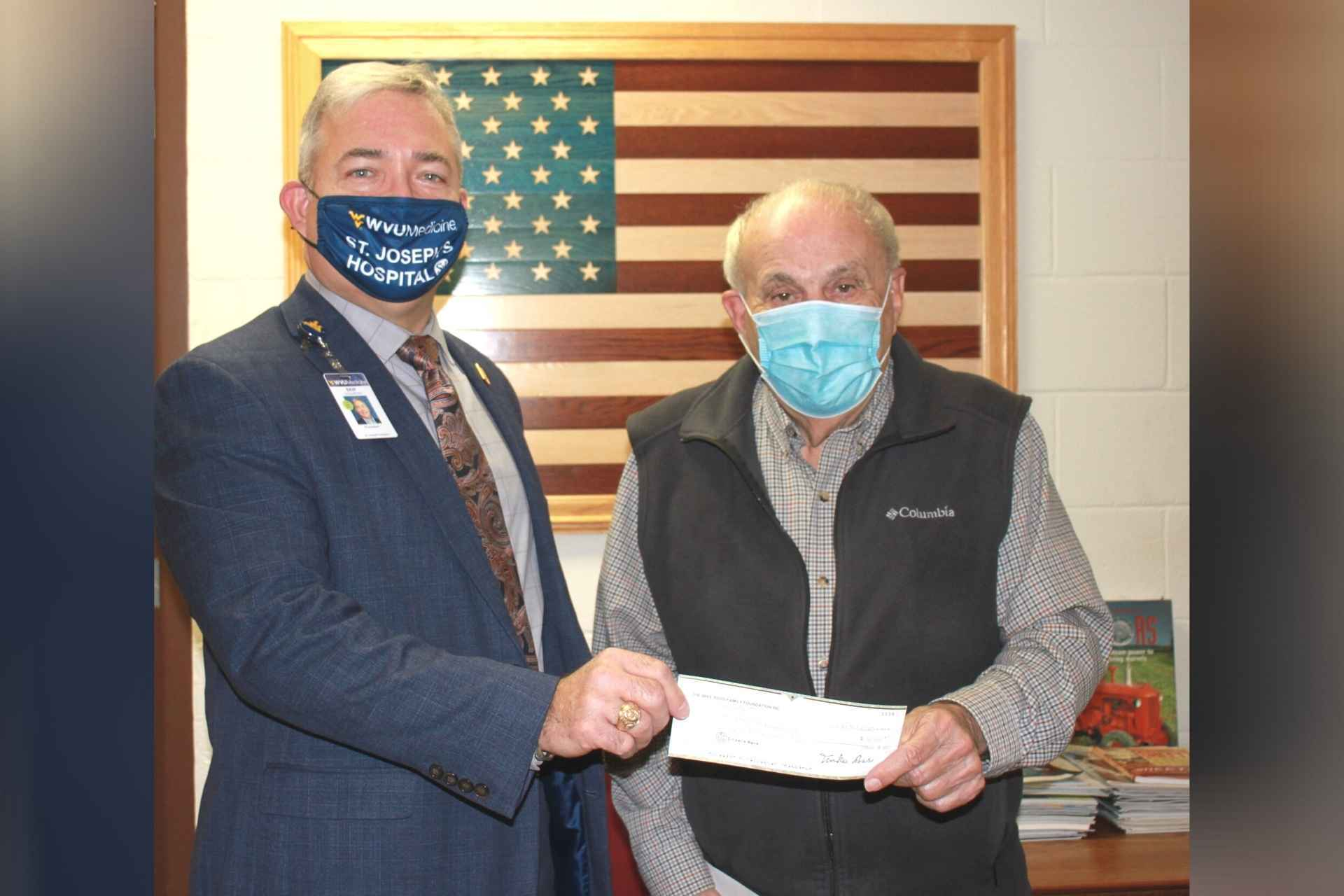 Businessman Mike Ross, right, presents a donation to St. Joseph's Hospital president Skip Gjolberg.