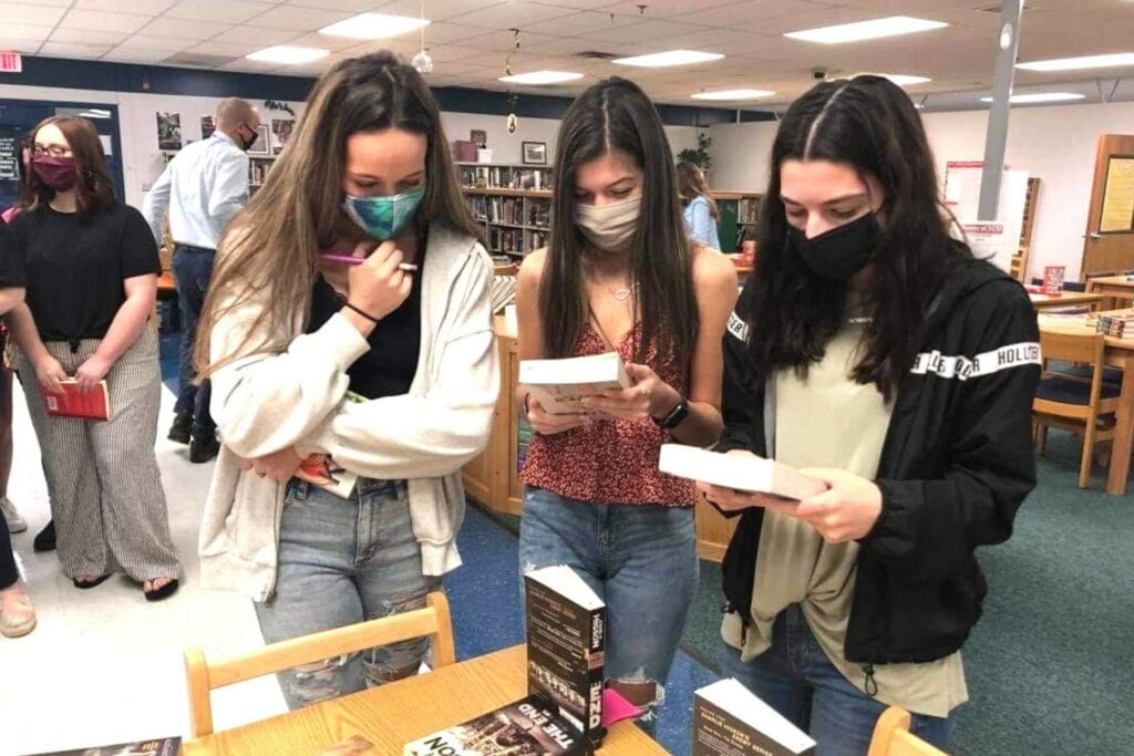 Buckhannon-Upshur High School students Kloey Chapman, Bella Weatherholtz and Olivia McKisic browse books donated by West Virginia Read Aloud during a recent event at the school celebrating School Library Week. More than 1,000 books were donated to the school so students could select the perfect book to help rekindle the love of reading.