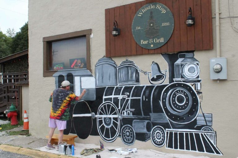 Artist Sheri Gaudet works on a new mural on the side of the Whistle Stop.