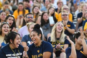 Students laugh as they enjoy the 2021 Monday Night Lights event at Milan Puskar Stadium. The Class of 2025 Welcome Week event was held Sunday, Aug. 22, after it was postponed because of weather the previous week. (WVU Photo/Jennifer Shephard)