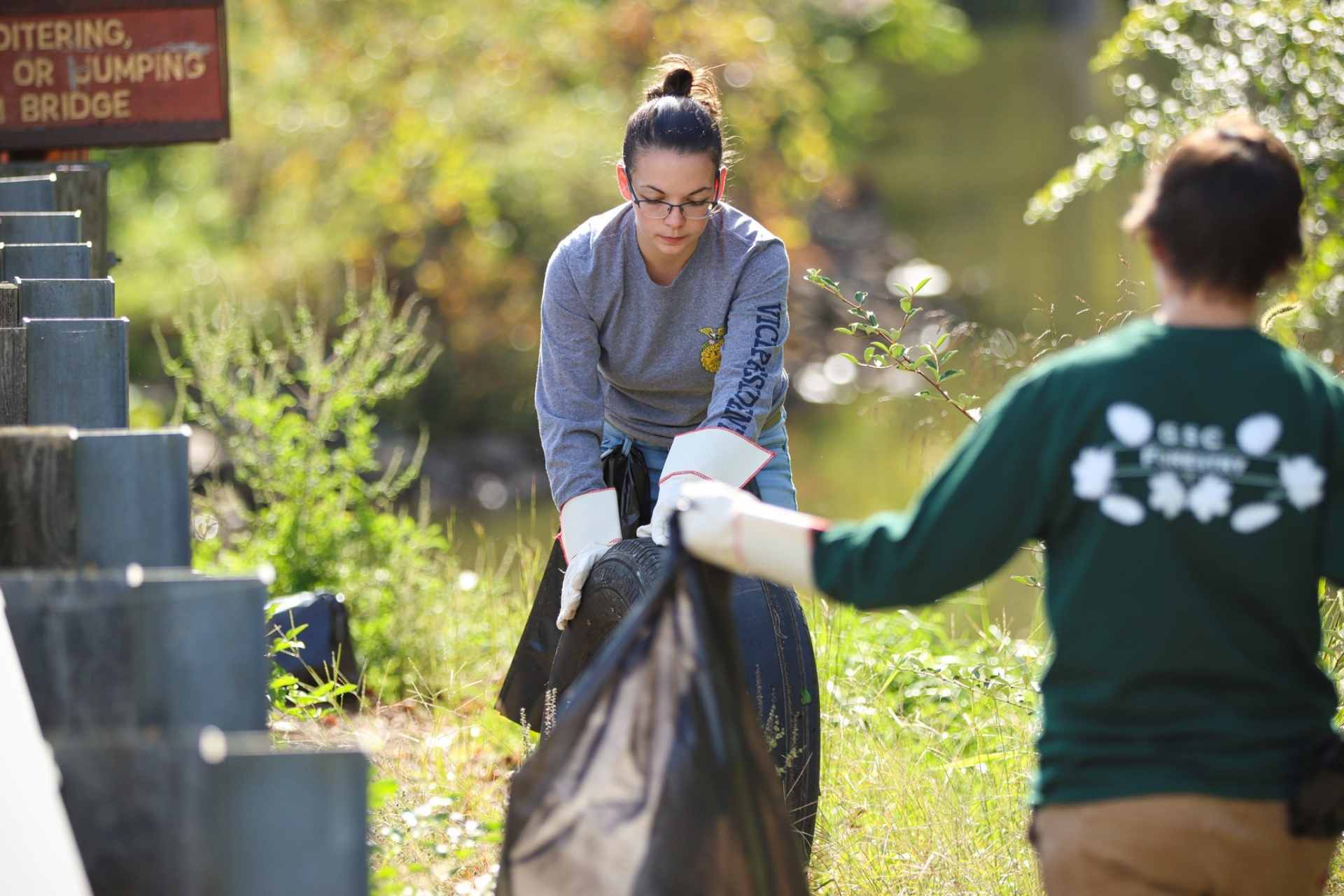 Glenville State College Natural Resource Management students Katlyne Rollyson (center, with tire) and Lexi Pletcher clear trash from around Stonewall Jackson Lake during a recent volunteer clean-up event.